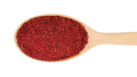 condiments: Sumac on a wooden spoon. isolated on a white background