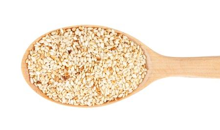 I semi di sesamo su cucchiaio di legno. isolato su uno sfondo bianco