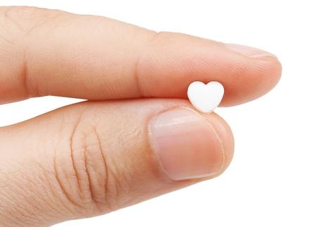 comprimido en los dedos aislados sobre un fondo blanco