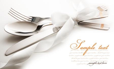 cuchillo y tenedor: cubiertos - cuchillo, cuchara y tenedor atado cinta. aislado en un fondo blanco