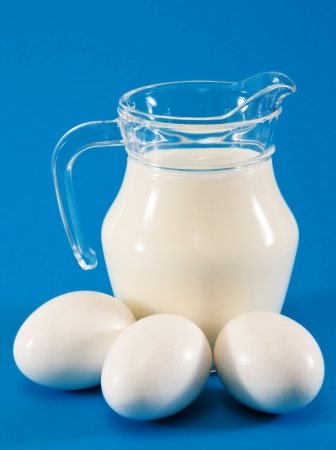 jug of milk and three white eggs on a blue background  photo