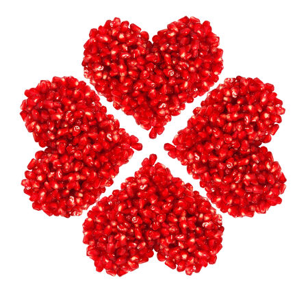 pomegranate seeds in heart shape isolated on white background photo