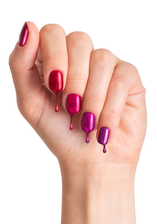 Female hand with painted nails in different colors. Nail polish dripping on nails