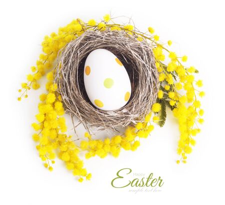 huevo blanco: Easter egg in a nest with a branch of mimosa isolated on white background Foto de archivo
