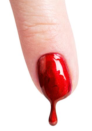 uñas pintadas: Female nails painted red. Nail polish dripping on the nail