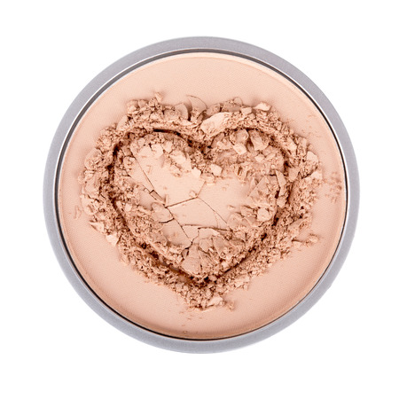 Face powder. Face powder in the form of heart. Make up crushed powder. Isolated on white background Фото со стока