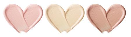 Uitstrijkjes van foundation voor gezicht.Een uitstrijkje van lippenstift. Cosmetisch uitstrijkje van vloeistof. Geïsoleerd op witte achtergrond