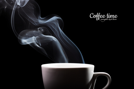 Fragrant coffee on a black background for your advertising. Smoke from hot coffee. Foto de archivo