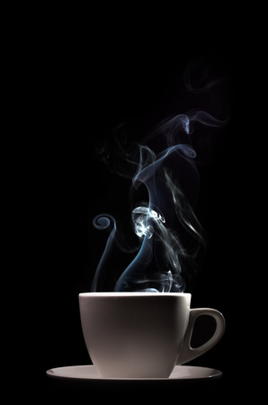 Fragrant coffee on a black background for your advertising. Smoke from hot coffee. Banco de Imagens