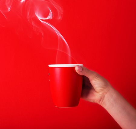 Woman with a cup of fragrant coffee in her hands on a cool day. Black warm coffee in cold weather.Coffee on a red background for your design. Advertising coffee. Stock Photo