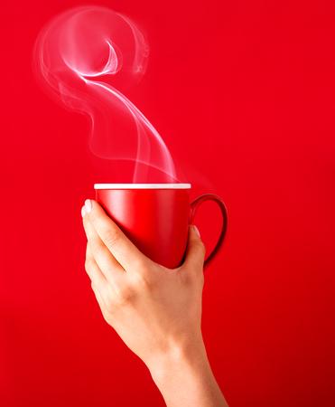 Frau mit einer Tasse duftendem Kaffee in den Händen an einem kühlen Tag. Schwarzer warmer Kaffee bei kaltem Wetter. Kaffee auf rotem Hintergrund für Ihr Design. Werbung für Kaffee.