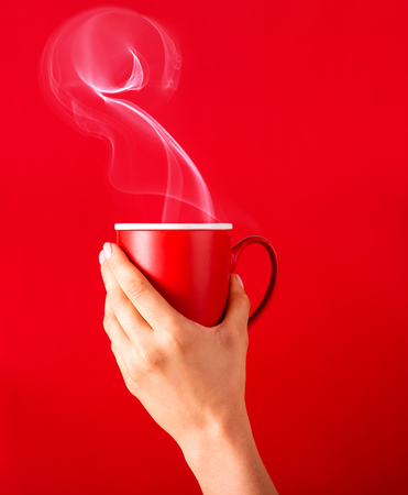 Kobieta z filiżanką pachnącej kawy w dłoniach w chłodny dzień. Czarna ciepła kawa w chłodne dni. Kawa na czerwonym tle do projektowania. Kawa reklamowa.