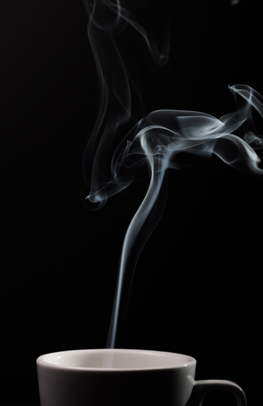 Fragrant coffee on a black background for your advertising. Smoke from hot coffee. Imagens