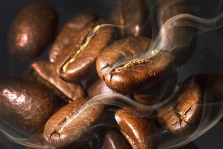 Roasted coffee beans. Seeds of freshly roasted coffee with smoke. Coffee beans closeup with emphasis on the grain with smoke. Stock Photo