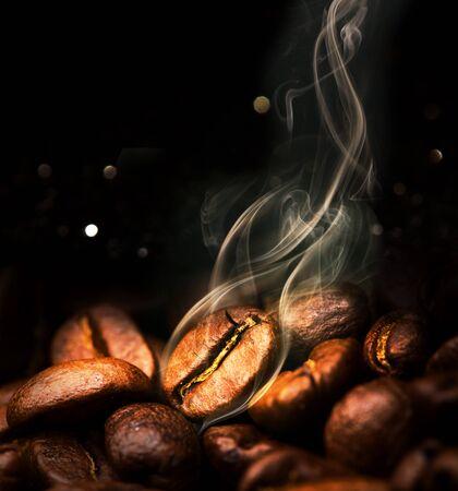 Geröstete Kaffeebohnen. Samen von frisch geröstetem Kaffee mit Rauch. Kaffeebohnen Nahaufnahme mit Betonung auf das Korn mit Rauch. Standard-Bild