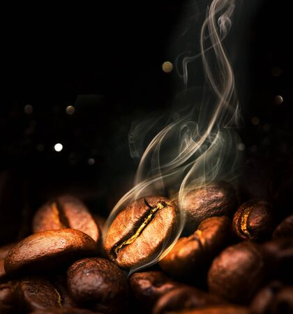 Roasted coffee beans. Seeds of freshly roasted coffee with smoke. Coffee beans closeup with emphasis on the grain with smoke. Фото со стока