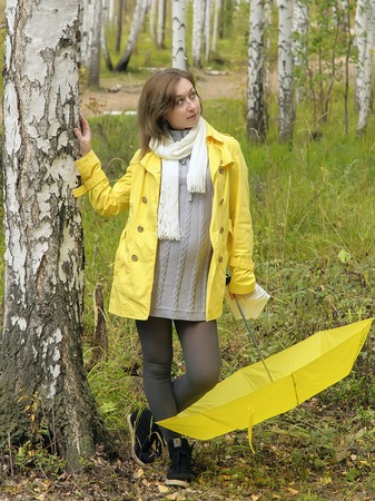 Outdoor closeup fashion portrait of young pregnant woman in autumn forest with yellow umbrella photo