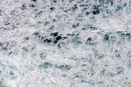 White waves on black volcanic pebble the beach