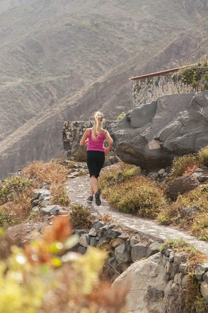 Fitness  Young woman running on a mountain road photo