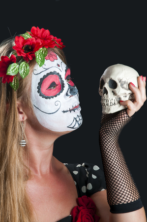 Portrait of young blond girl in black dress with Calavera Mexicana makeup mask and with Skull in her hand photo