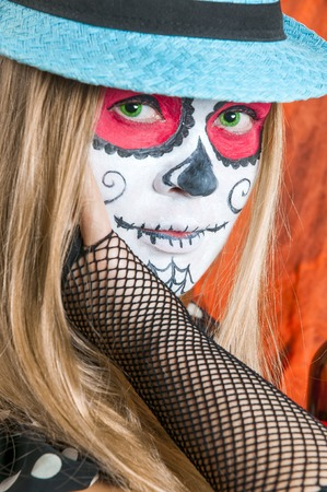 Girl with Calavera Mexicana makeup mask in the blue hat photo