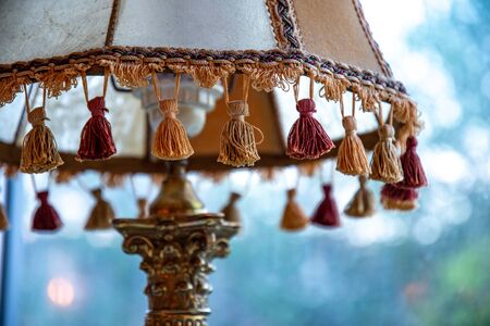 Closeup of brown tassels on antique lampshade with ornate bronze foot lamp element and blurry background. Vintage lamp details.