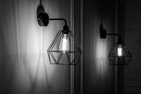 Black and white stock photo of modern pendant light in diamond shape wire lampshade with light bulb inside. Glowing filament in lamps of minimal style. Sconces hanging on wall. Interior lighting.