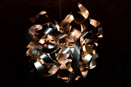 Metal ribbon chandelier closeup. Modern lampshade. Copper and silver textured background. Abstract chaotic pattern. Futuristic abstract backdrop in shades of brown.