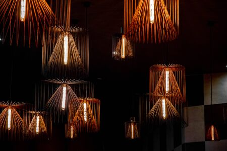 Group of different sizes geometric wire chandeliers hanging chaotically in darkness. Modern metal lampshades. Lamps with long light bulbs. Abstract background. Futuristic backdrop. Interior decoration