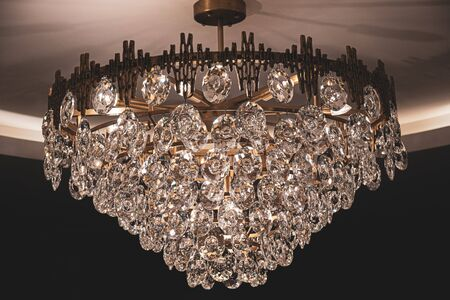 Pendant chandelier with sparkling crystal on dark background. Vintage shiny luster lamp closeup. Luxury interior decoration. Antique golden metal chandelier with shiny glass hangings.