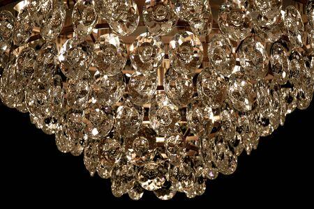 Glowing golden glass texture closeup. Sparkling crystal pendant hangings of luxury chandelier on black background. Vintage shiny glass surface macro. Hexagon pattern backdrop. Standard-Bild