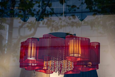 Blurry background of abstract reflections in glass window and gorgeous red chandelier with ornate crystal hangings behind the glass. Luxury pendant light through blurred glass.