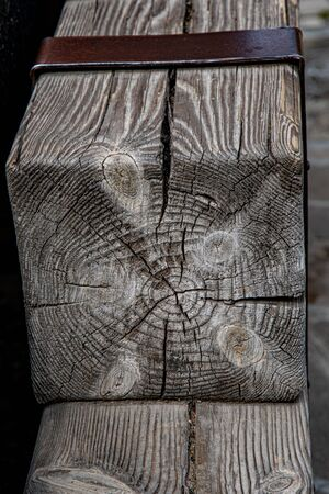 Cracked wooden texture of square wood block. Hardwood background in shades of grey and brown. Timber industry