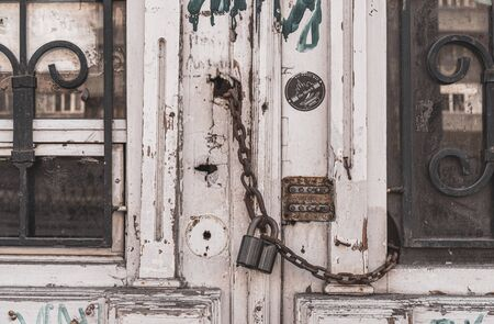 Architectural details of dirty white wooden door chained by old rusty metal padlock. Architecture of European city. Retro building exterior. Doorway of house facade.
