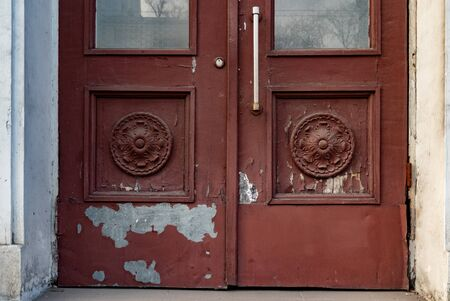Antique fretwork elements of old brown door with flaking paint and stains. Sculptural rosettes in square frames of door panels of classic building in Europe Archivio Fotografico