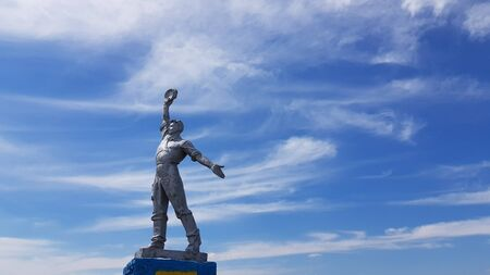 Historical Soviet art statue of worker in powerful pose with sky background. Social realism monument in Odessa countryside of Ukraine.