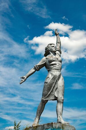 Powerful woman historical monument on blue sky with white clouds background. Social realism stone sculpture in countryside of Ukraine