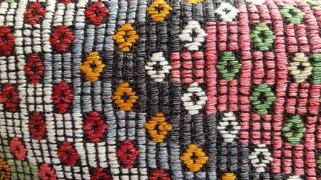Folk geometric rhombus pattern on handmade weaved rug. Turkish ornamental carpet background. Woven texture closeup. Ethnic ornamental fabric backdrop. Traditional Asian handmade cloth