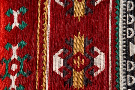 Ornate colorful weaved floor mat. Turkish ornamental carpet background. Woven texture. Ethnic pattern rug. Traditional Asian ornaments. Turkish bazaar backdrop