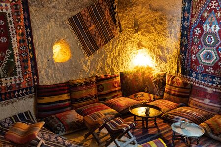 Traditional Turkish interior with vintage ornate carpets and cushions with striped ethnic ornaments. Small round coffee table in center of corner sitting zone in Asian interior. Turkish coffee time concept