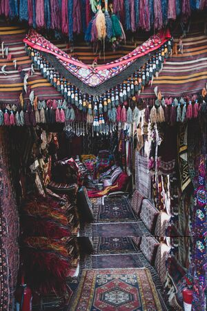 Turkish bazaar carpet shop entrance decorated with handmade rugs with colorful tassels. A lot of different weaved carpets. Woven texture. Ethnic pattern rugs. Traditional Asian ornaments Standard-Bild