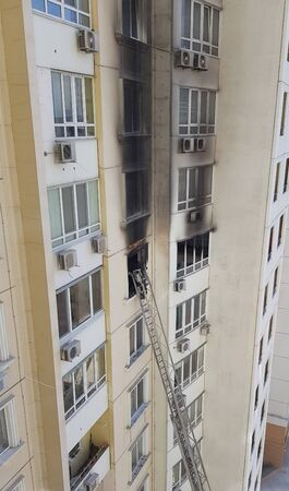 Firefighting laddes to window with black smoke after fire in building. Accidents due arson in protests 版權商用圖片