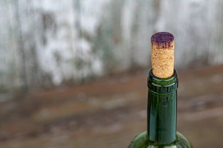 Closeup of wine bottleneck closed with cork stopper stained by dark purple red wine. Top of green glass bottle on distressed wood background with copy space.