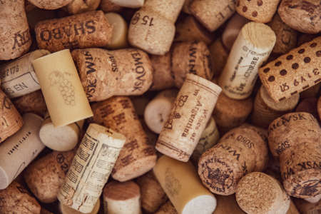 Odessa / Ukraine - 05 28 2020: Selective focus to wine cork with grape bunch drawing and blurred background of messy wine corks. Collection of different wine bottle corks for winery concept background Redakční