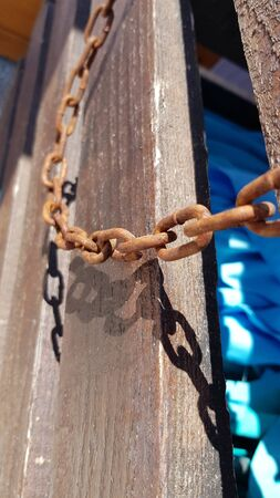 Old rusty metal chain links closeup on rough wooden background in bright sunlight with dark shadows. Broken iron chains as freedom slavery symbol Foto de archivo