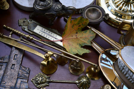 Flat lay of vintage ornate objects and autumn maple leaf near retro thermometer. Flea market antique stuff and colorful fall leaf closeup