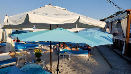 Blue and white sunshades and parasols on clean beach sand. Tranquil landscape with beach umbrellas and wooden flooring footpath at resort 写真素材