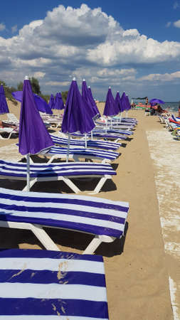 Perspective view to row of striped chaise-longues and purple closed parasols on clear beach sand with wood flooring path along. Amazing cloudscape above summer beach
