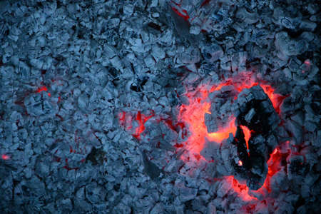 Big cracked piece of smoldering firewood log with red flame inside and gray ashes background. Burnt campfire texture closeup. Burning wooden coal surface Stock Photo