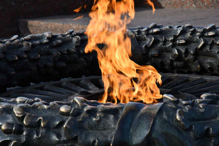Eternal flame at monument of unknown sailor soldiers of the Second World War in Odessa city park of Ukraine. Closeup of burning fire in bronze sculptural memorial